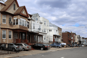 Houses on a street with telephone wires in moderate- to-low income neighborhood