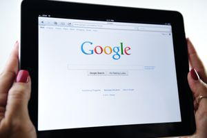 Hands hold an iPad displaying the Google website