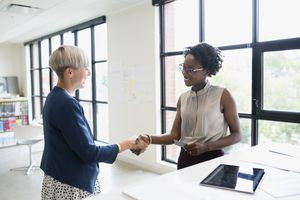 female colleagues shaking hands in office