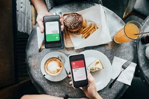 Overhead view of friends sending/receiving the payment of the meal through digital wallet device on smartphone while dining together in a restaurant