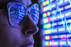 Stock analyst viewing financial market data on screen