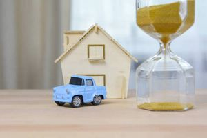 Toy car parked in front of miniature home and next to a sand timer, symbolizing time is running out to change auto insurance after moving to a new state