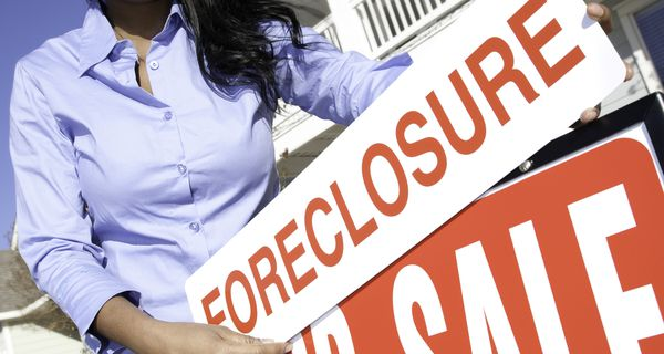 Woman Putting Up Foreclosure Sign at House