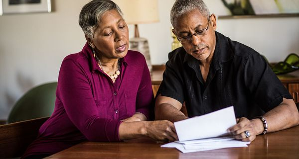 Senior couple paying bills at home