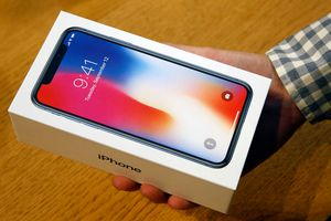 A customer holds a box containing an Apple iPhone X.