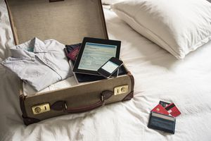 Open suitcase on bed with digital tablet and phone