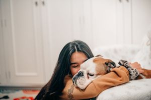Young woman taking care of her dog