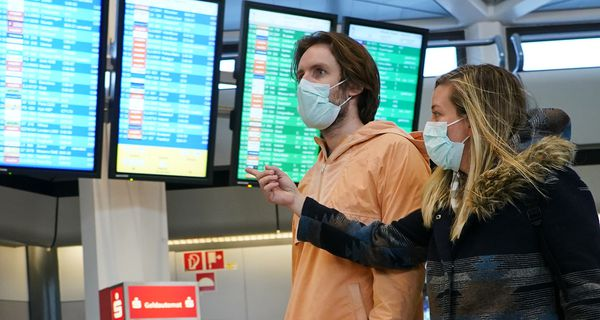 Young couple in face masks at the airport