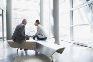 Business people reviewing paperwork in modern lobby