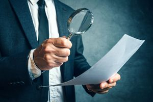 A Man Holding a Magnifying Glass Over Paper