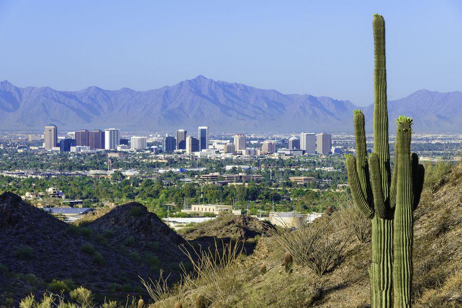 Phoenix skyline framed by saguaro cactus and mountainous desert