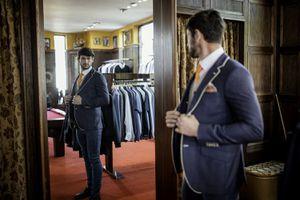 Man Admiring Himself in a Mirror in a Menswear Shop