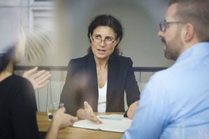 lawyer discussing with businessman and businesswoman during meeting at office