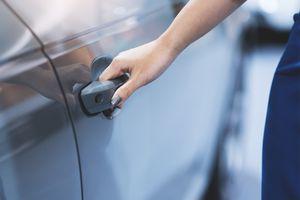 A woman's hand opening a car door