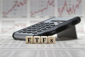 ETF Letters on Wooden Cubes on a Blurred Business Newspaper