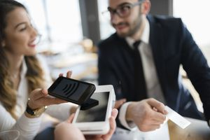 Business Executives Completing Transaction With Mobile Phone