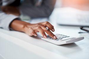 A businesswoman using a calculator at her desk in a modern office.