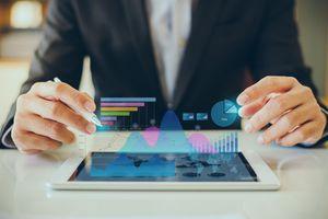 Businessperson analyzes market data on a tablet