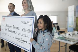Girl helping hold large donation check in community center