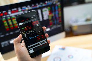 Hand Holding Smart Phone Displaying Stock Market Data