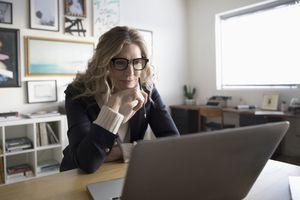 Businesswoman entrepreneur working at laptop in studio office.