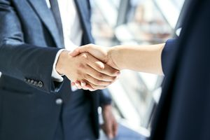 Close-up of handshake of businesswoman and businessman.