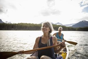 Mature couple canoeing on tranquil lake, Alberta, Canada