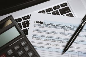 Printed Tax Form on Laptop With Calculator and Pen