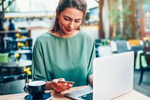 A woman in a green shirt uses a credit card to shop on her laptop while she sits in a coffee shop