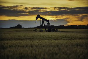 Oil pump in the middle of a field during sunset