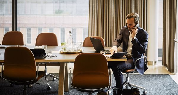 legal professional talking on mobile phone while writing in diary at board room