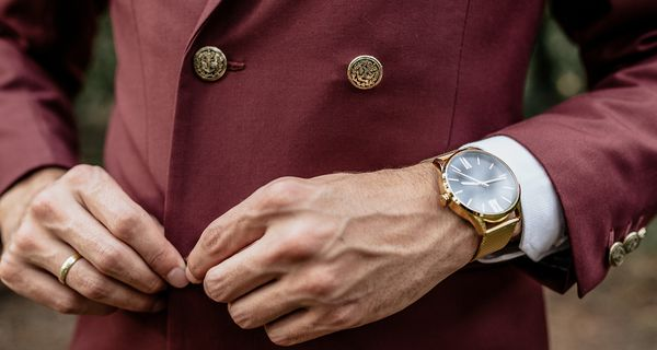 Close-up of man wearing a suit and golden watch buttoning his jacket