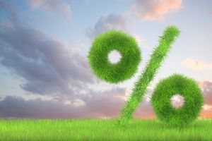 A percentage sign made of grass on a cloudy backdrop