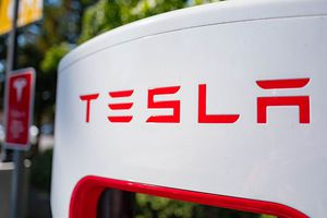 Close up of Tesla logo on a charger at a Supercharger rapid battery charging station for the electric vehicle company Tesla Motors.