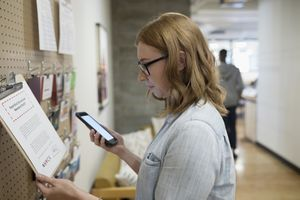 Female freelancer with smart phone checking message board in office.