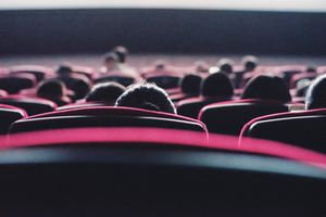 A rear view of people sitting in a movie theater.