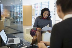 Businesswomen reviewing paperwork in office lobby.
