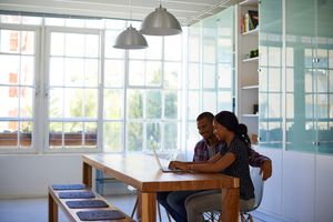 Young couple looking at laptop in bright kitchen.