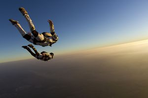 Two people skydiving at sunset