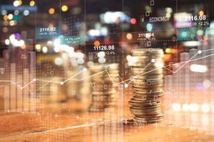 A double exposure with business charts, a stack of coins and a night city background.