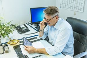 Mature Businessman Sitting at His Desk Using a Phone While Holding a Tablett PC
