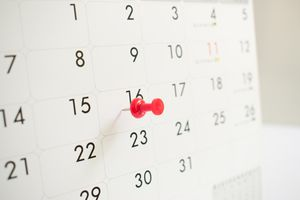 Close-up of a calendar with a pin on a date