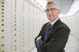 Businessman Standing In Safety Deposit Vault.