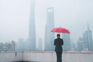 A businessman holds a red umbrella