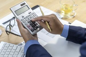 An Accountant working on a calculator while sitting at a desk.