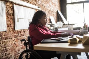 A woman seated in a wheelchair at a desk working on a laptop.