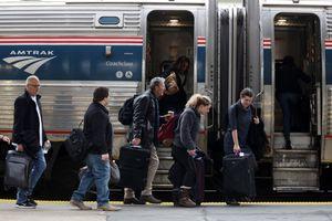 Passengers wait to board an Amtrak train.
