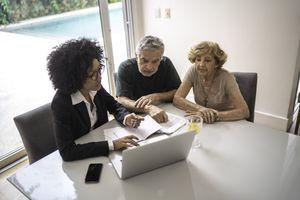 A financial advisor helping a senior couple at home.