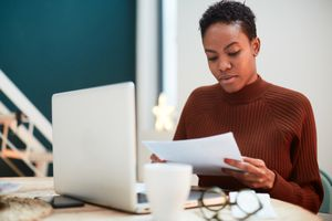 Woman working on her finances at home, filling out tax forms