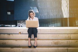 Young woman sits on steps outdoors, working on a laptop